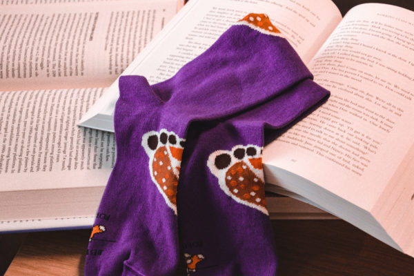 A pair of purple Best Foot Forward socks rest atop two open books.