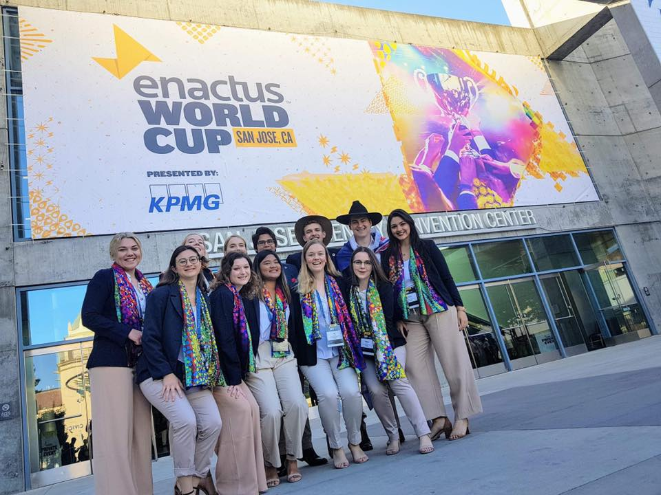 The Enactus QUT team stands outside the Enactus World Cup wearing Best Foot Forward scarves.