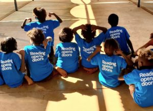 Seven Indigenous children sit on a concrete floor, with their backs to the camera. They wear blur shirts that say 'Reading opens doors'.